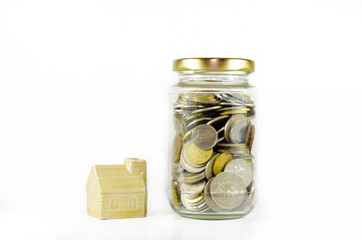 Miniature dream house beside closed glass jar filled with coins isolated on white background.