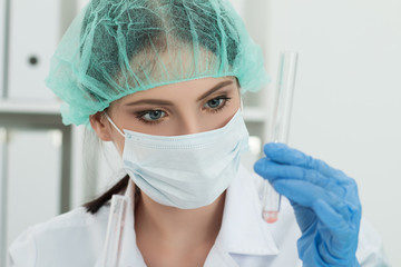 Medical doctor in protective gloves and surgical mask and hat lo