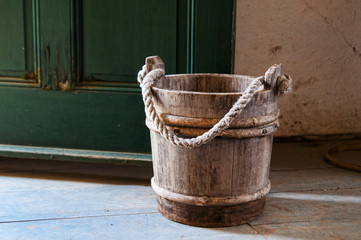 old fashion wooden pail by a green door