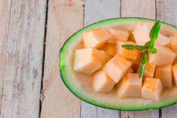 Cantaloupe, cut into pieces, put on a wooden background.
