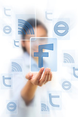 Hand holding facebook icon on touch screen pad