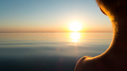 The boy looks at the sunset over the sea