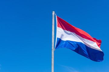 Dutch flag against blue sky