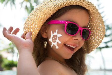 Happy child in glasses with sunscreen on the face