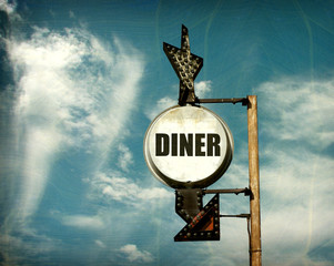 aged and worn vintage photo of diner sign with arrow