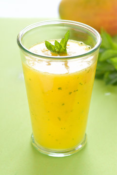 Cooling Mango mint smoothie, summer drink on green table, Yellow Tropical Smoothie made with mango, mint and lime juice.