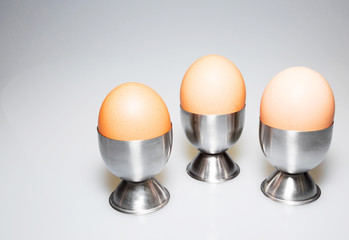Three eggs in the stands on isolated white