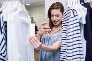 Brunette taking a photo of price tag