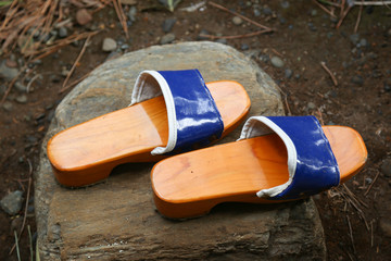 Traditional Japanese Zen Wooden Shoes on a Rock in a Garden.