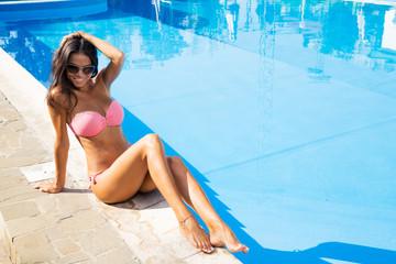 Charming woman sitting in bikini near swim pool