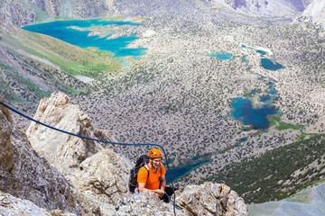Mountain climber over abyss Elder man orange jacket protection helmet holding belaying rope rocky cliff arranging descent wild vivid color mountain lakes on background
