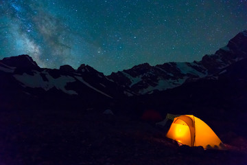 Night mountain landscape with illuminated tent Silhouettes of snowy mountain peaks and edges night sky with many stars and milky way on background illuminated orange tent on foreground