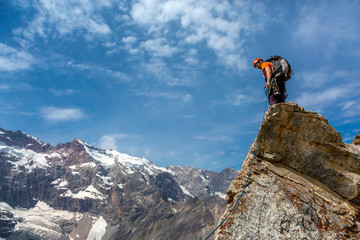 Mountain climber on top Rocky razor sharp pointed summit and silhouette of male climber staying on sky and remote high land ridge background daylight sunny day outdoors