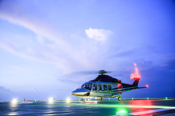 Foto op Plexiglas Helicopter helicopter parking landing on offshore platform. Helicopter transfer crews or passenger to work in offshore oil and gas industry.Night flight training of Pilot and coordinate pilot.