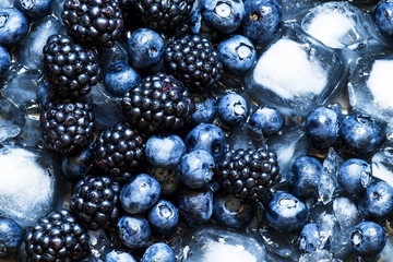 Blackberries and blueberries in ice on a dark background, select