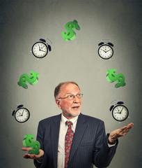 business man juggling multiple alarm clocks and dollar sings