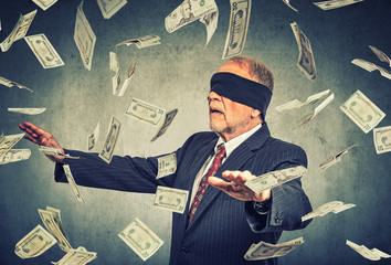 Blindfolded senior businessman trying to catch dollar bills banknotes
