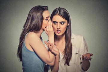 Girl whispering into woman ear telling her shocking secret