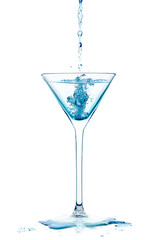 Blue Liquid falling into a cocktail glass of dry martini Isolate