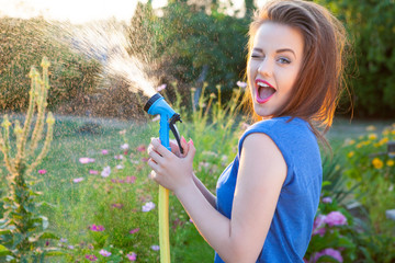 Playful young attractive winking woman with water hose watering plants, gardening concept