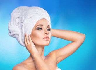 A beautiful girl with a towel on his head, rubs face with his hand.