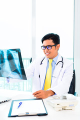 Asian doctor examining x-ray picture in practise