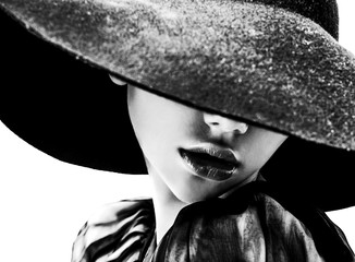Beautiful woman with full lips in black hat poses on white
