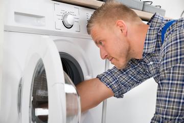 Handyman Repairing Washing Machine