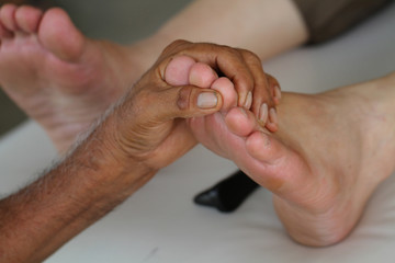 Close up foot massage by old man's hands