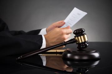 Judge Holding Document At Desk