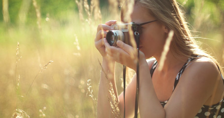 Girl taking photos in nature with vintage camera