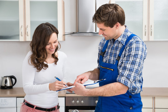 Woman Writing On Clipboard With Plumber In Kitchen Room