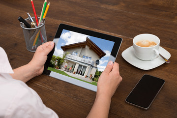 Businessperson Looking At House Photo On Digital Tablet