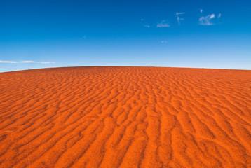 A rippled red sand dune against a clear blue sky, taken near Uluru in central Australia