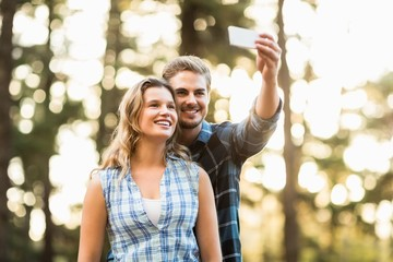 Happy smiling couple embracing and taking selfies