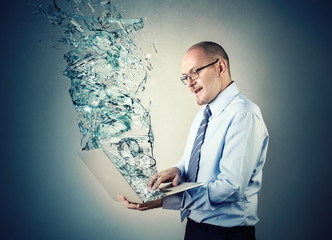 Businessman holding a pc with a vortex of water coming out of it
