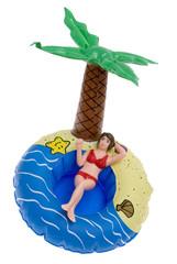 Puppe auf einer Badeinsel mit Palme