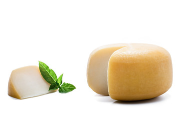 Yellow round cheese with a piece and basil leaves on white background