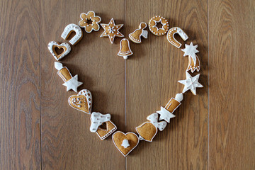 Christmas background with cookies on the wooden board (heart shape frame)