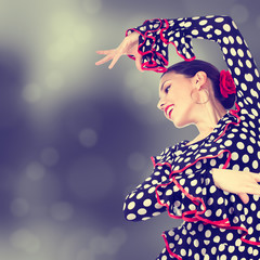 Close-up portrait of a young woman dancing flamenco on abstract background