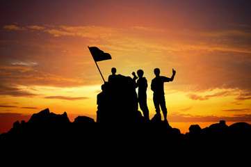 Silhouette of a champion on mountain peak at sunset.