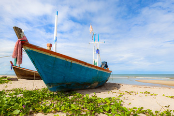 Fishing boat on sand beach and blue sky