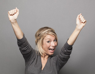 extrovert 20s blonde woman raising hands for victory