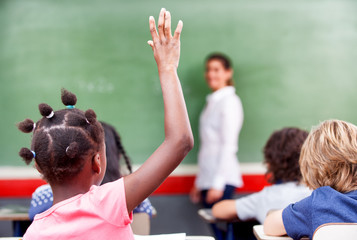 Happy schoolchildren at primary school raising hand in elementar