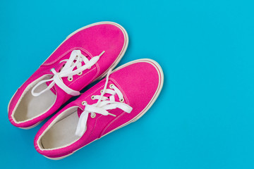 Pink sneakers with laces on a blue