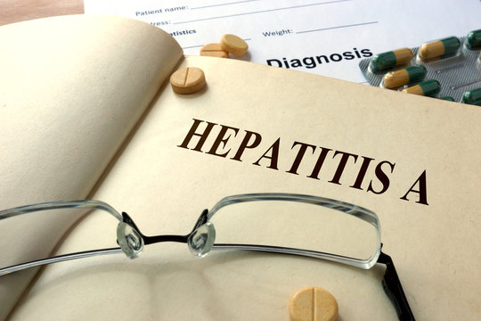 Word Hepatitis A  on a book and pills.
