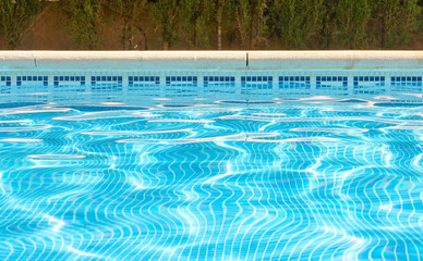 Picture of water at the surface of a swimming pool including tiled side and pool edge. With copy space