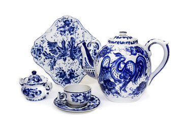 Porcelain teapot, cup, saucer, sugar bowl and dish in folk style painted blue on white background