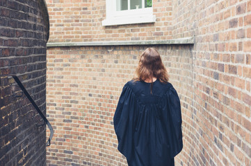 Woman in graduation gown on stairs