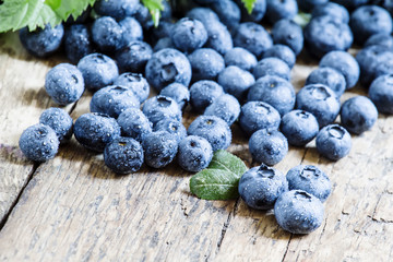 Fresh blueberries and green leaves on the old wooden background,